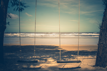 Wooden swing hanging from tree on the beach with seascape view background in vintage style. Stok Fotoğraf - 83701843