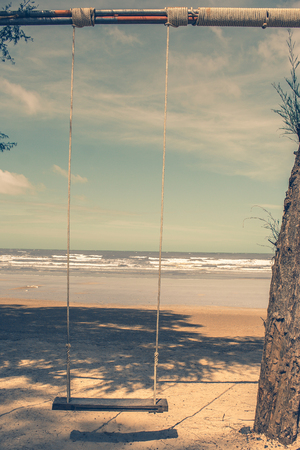Het houten schommeling hangen van boom op het strand met de achtergrond van de zeegezichtmening in uitstekende stijl.