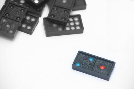 Close-up zwarte kleur domino's met kleurrijke stipjes liggen op een witte achtergrond. Stockfoto