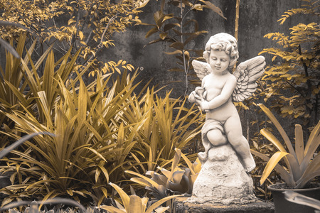 Little white cupid sculpture in outdoor garden. (Vintage filter effect)