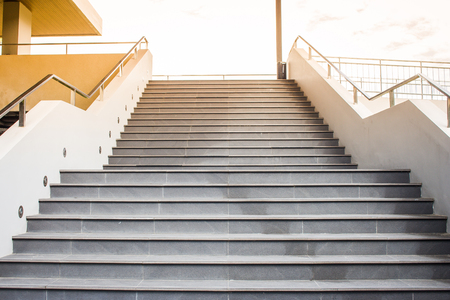Empty concrete staircase with metal railing going up to the top with sunlight background.