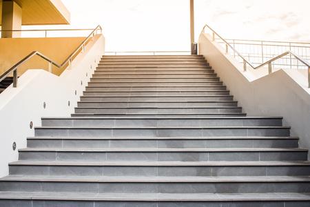 Lege concrete trap met metaaltraliewerk die tot de bovenkant met zonlichtachtergrond gaan.