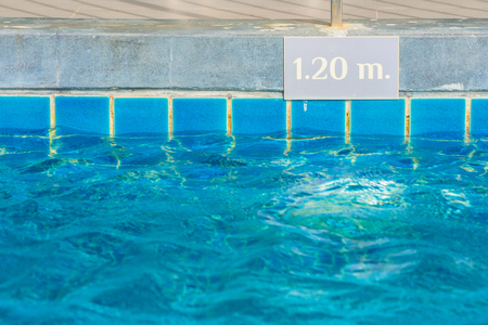 Blue water in swimming pool with depth of the pool warning for information for people's safety. Stok Fotoğraf - 84050061