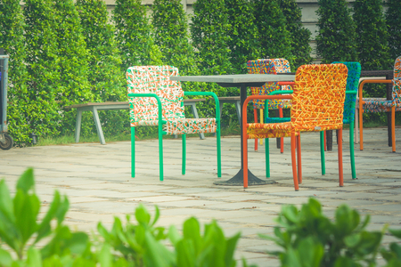 Abstract colorful plastic weaving rattan chair standing on concrete floor. (Vintage filter effect) Stok Fotoğraf - 84049940