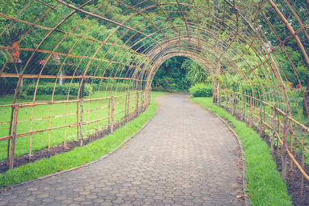 Bamboo wooden tunnel walkway or footpath in public park. (Autumn filter effect)