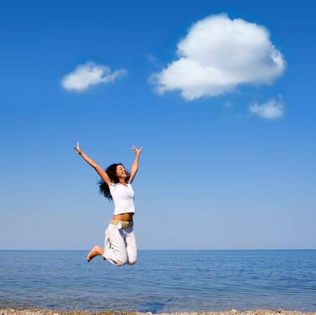 happy young woman is jumping in the beach  photo