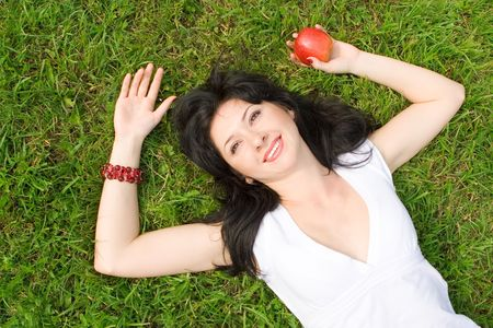 pretty woman eating green apple on the summer glade  photo