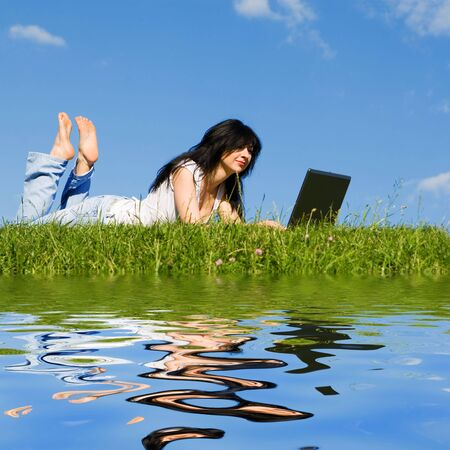 mobility: pretty woman with laptop on the green grass