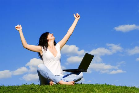 pretty woman with laptop on the green grass photo