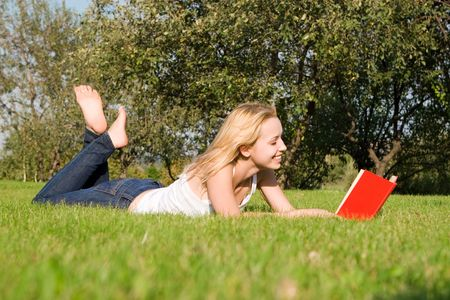 young blonde reads book in the park Stock Photo - 3791077