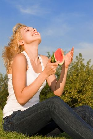 young blonde eats watermelon in the park photo