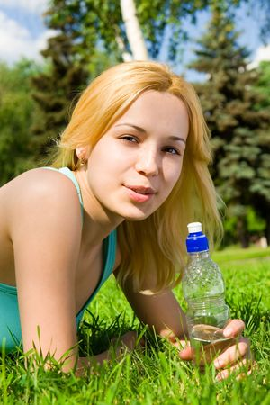 pretty woman drinking water on the summer glade photo