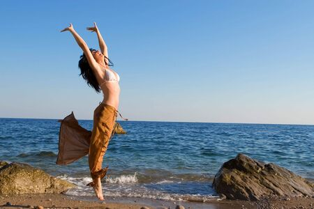happy young woman dance in the beach photo