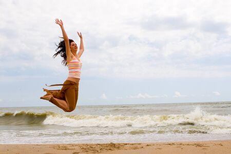 salto largo: feliz joven salta en la playa