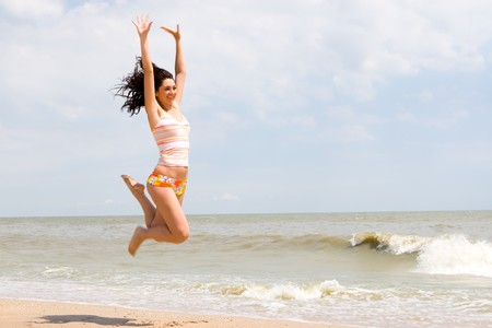 high jump: happy young woman is jumping in beach