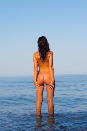 naaktstrand: Mooie jonge vrouw op de zee