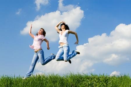 dos mujeres saltando feliz en la hierba verde Foto de archivo - 4563684