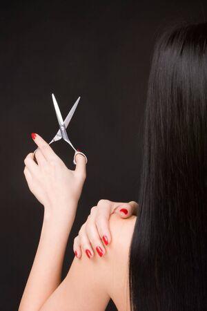 Lovely brunette with scissors of the hairdresser