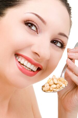 young woman eating muesli isolated on the white background photo