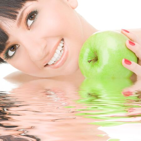 sweet girl eating green apple on white background photo