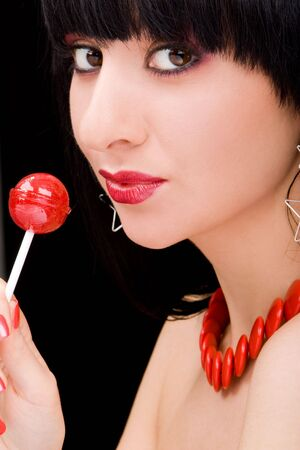 sweet woman with candy on black background  photo