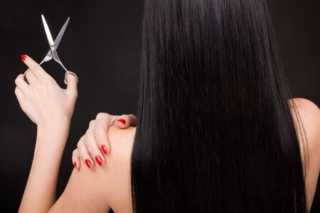 hairdresser cutting hair: brunette with scissors of the hairdresser