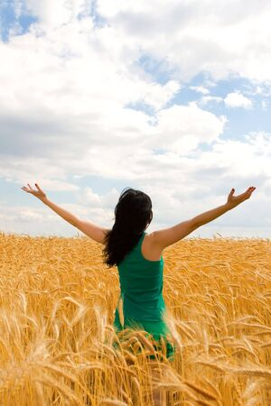 Happy woman in golden wheat photo