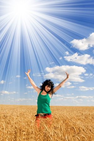 Happy woman jumping in golden wheat