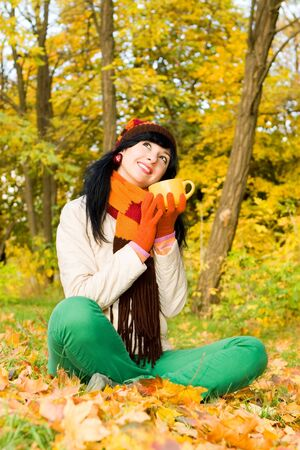 forest tea: Young pretty woman with cup of tea in the autumn park