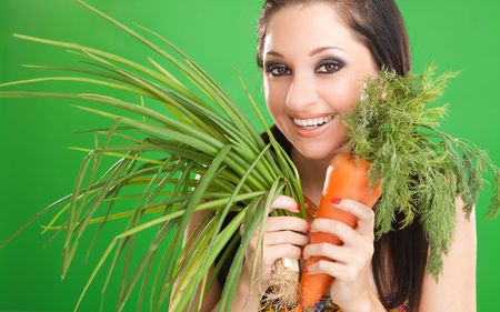 Pretty girl with carrot and onion on the green background  photo