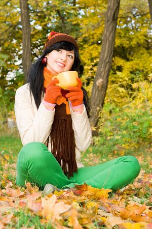 Young pretty woman with cup of tea in the autumn park  photo