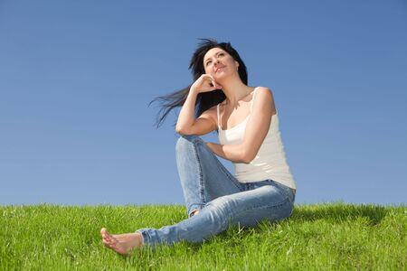 young woman rest on the green grass photo