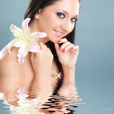 Young woman with lily flower on the blue background Stock Photo - 5591686