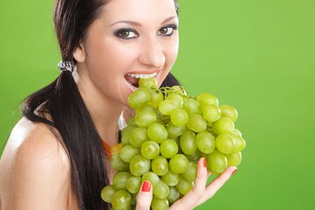 Pretty woman with grape on the green background Stock Photo - 5613510