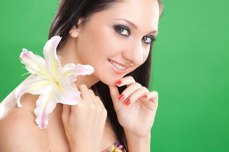 Young woman with lily flower on the green background  photo
