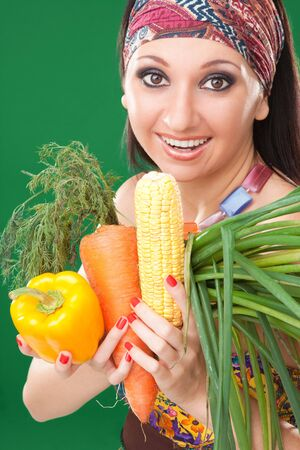 Pretty girl with vegetables on the green background Stock Photo - 5620628