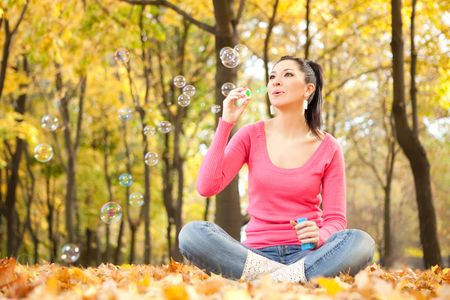 Young woman blowing soap bubble in the autumn park photo