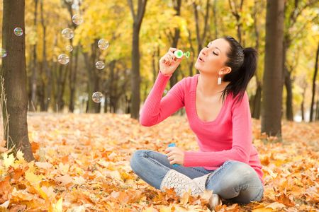 Young woman blowing soap bubble in the autumn park Stock Photo - 5751362