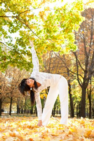 Pretty woman doing yoga exercises in the autumn park photo