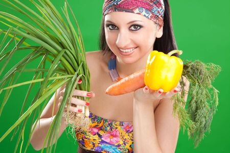 Pretty girl with vegetables on the green background  photo