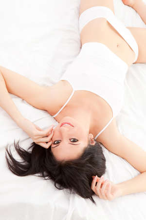 Sexy woman lying on the white bed Stock Photo - 6491036