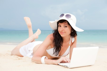 Cute woman with white laptop on the summer beach Stock Photo - 7258684