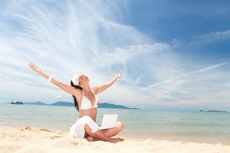 Cute vrouw met witte laptop in de zomer strand  Stockfoto