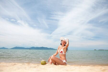 Young fashion woman with coco on the beach photo
