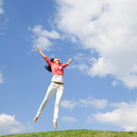 pretty young woman jumping on green grass Stock Photo - 7317903