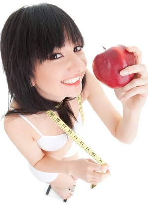 Fun woman with red apple and measure tape on the glass scales  photo