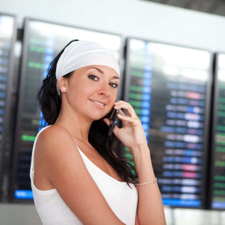 Young pretty woman talking on mobile phone in the airport  photo