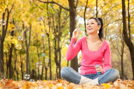 Young woman blowing soap bubble in the autumn park Stock Photo - 7992229