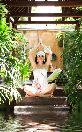 resort life: Young woman meditating on the tropical view Stock Photo