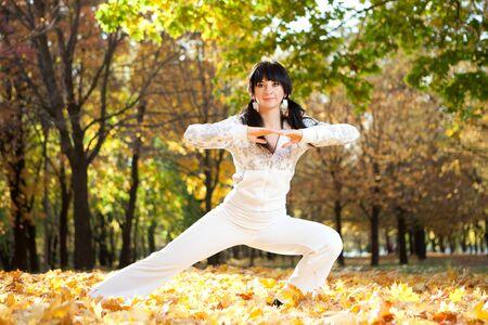 Pretty woman doing yoga exercises in the autumn park photo
